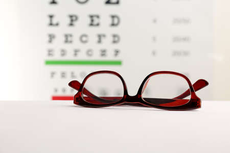 Glasses With Corrective Lenses On Table Against Eye Chart Stock ...
