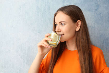 Young woman drinking lemon water on color background