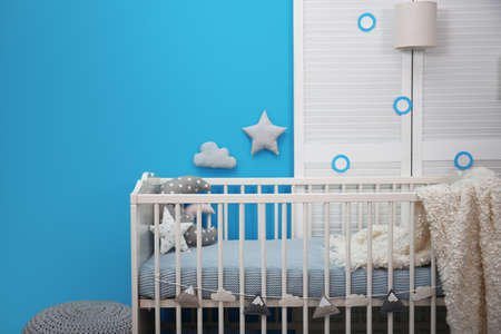 Baby room interior with crib near color wall Banque d'images