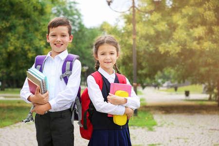 Cute little school children with stationery in park 免版税图像