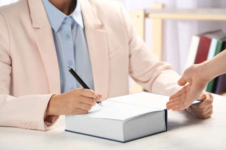 Writer signing autograph in book at table, closeup Stock Photo