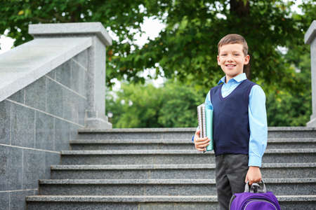 Cute school child with stationery near stairs in park