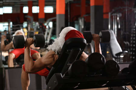 Young muscular man in Santa costume training with dumbbells at modern gym