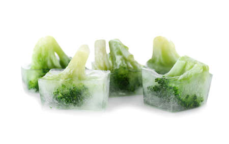 Fresh broccoli in ice cubes on white background. Frozen vegetables