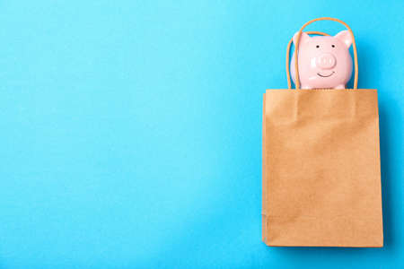 Flat lay composition with shopping bag and piggy bank on color background Imagens