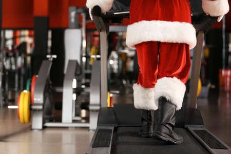 Authentic Santa Claus training on treadmill in modern gym, focus on legs