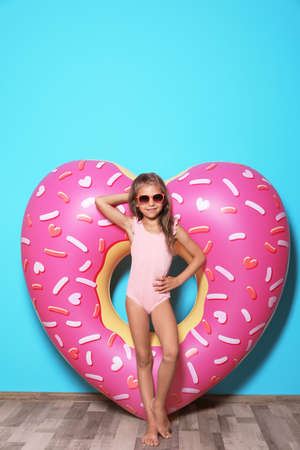 Cute little girl with bright heart shaped inflatable ring near color wall