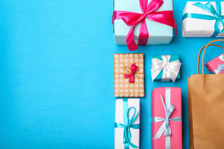 Flat lay composition with shopping bag and gifts on color background