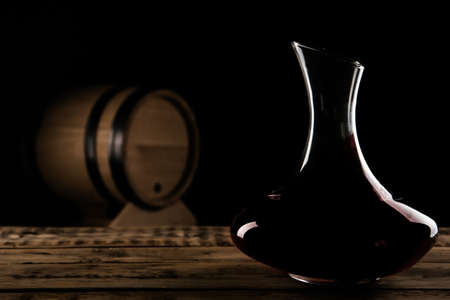 Elegant decanter with red wine on table against dark background