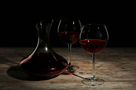 Elegant decanter and glasses with red wine on table against dark background Stock Photo