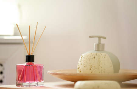 Aromatic reed air freshener and toiletries on table indoors