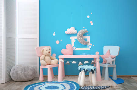 Modern interior of child game room with table, chairs and toys Standard-Bild