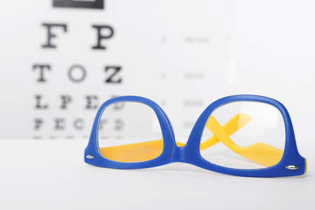 8b611c8f1122 Glasses with corrective lenses on table against eye chart Stock Photo -  106544195