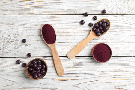 Flat lay composition with acai powder and fresh berries on wooden background Stock Photo