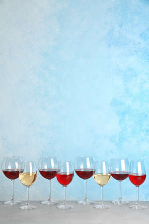 Glasses with different wine on table against color background