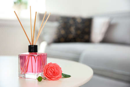 Aromatic reed air freshener and rose on table indoors