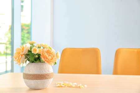 Vase with blooming flowers on table indoors