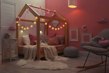 Child's room interior with comfortable bed and garland Stock Photo