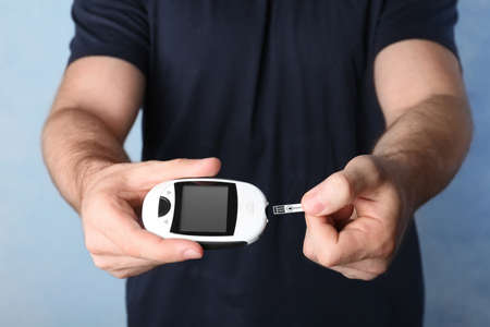 Man holding glucometer on color background. Diabetes test