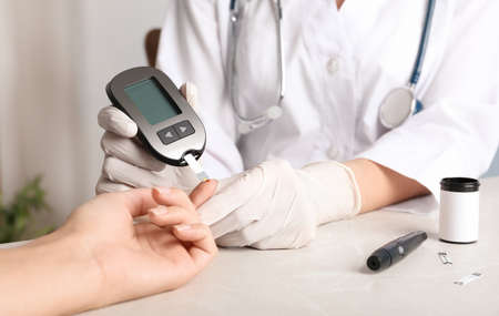 Doctor checking blood sugar level with glucometer at table. Diabetes test Stock Photo