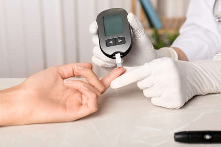 Doctor checking blood sugar level with glucometer at table. Diabetes test Reklamní fotografie