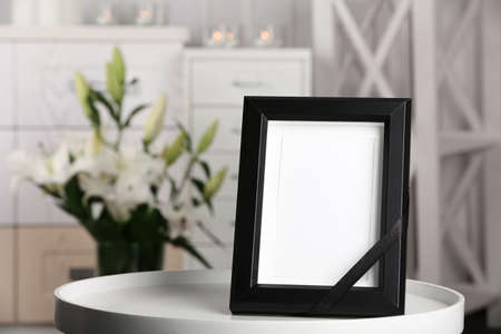 Funeral photo frame with black ribbon on table, indoors Archivio Fotografico