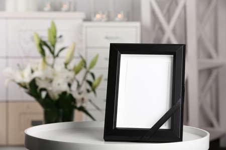 Begräbnisfotorahmen mit schwarzem Band auf Tisch, drinnen Standard-Bild