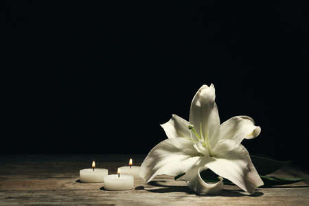 Beautiful lily and burning candles on dark background with space for text. Funeral flower 免版税图像 - 106561194
