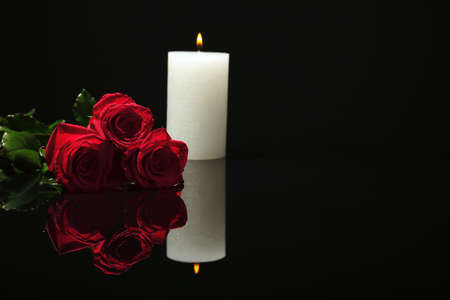 Beautiful red roses and candle on black background. Funeral symbol