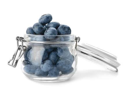 Glass jar full of fresh ripe blueberries on white background