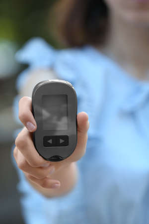 Woman holding digital glucometer on blurred background. Diabetes control Banque d'images