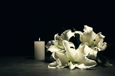 Beautiful lilies and burning candle on dark background with space for text. Funeral flowers