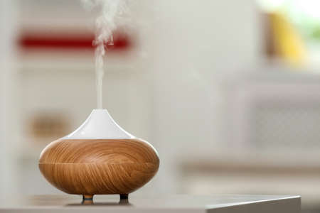 Aroma oil diffuser lamp on table against blurred background Фото со стока