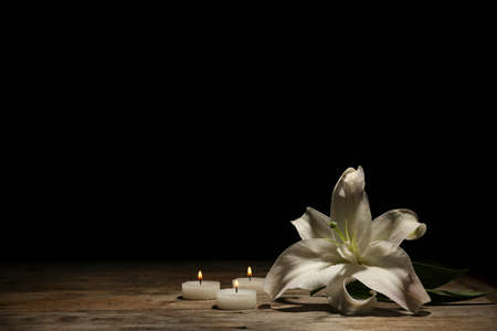 Beautiful lily and burning candles on dark background with space for text. Funeral flower 写真素材 - 106621285