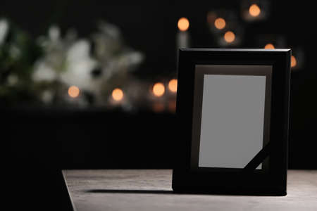 Funeral photo frame with black ribbon on table in dark room Stock Photo