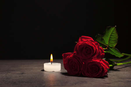 Beautiful red roses and candle on table against black background. Funeral symbol