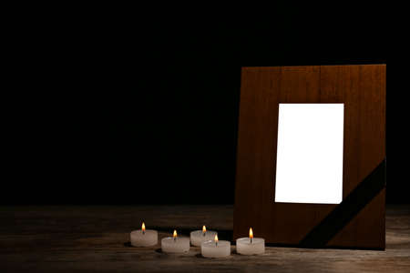 Empty frame with black ribbon and candles on table. Funeral symbol Stock Photo
