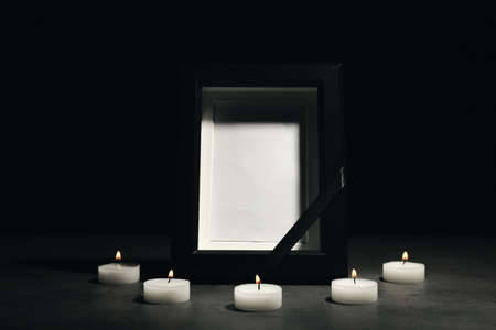Funeral photo frame and burning candles on dark background