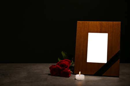 Empty frame with black ribbon, candle and roses on table. Funeral symbol Stock Photo