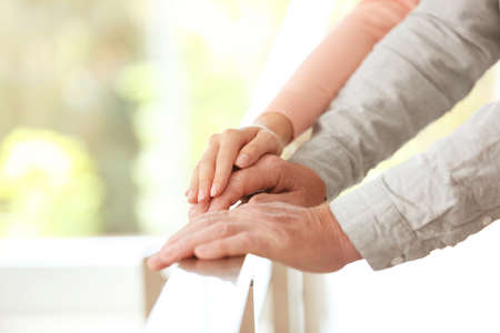 Young woman holding elderly man hand on railing indoors, closeup. Help service