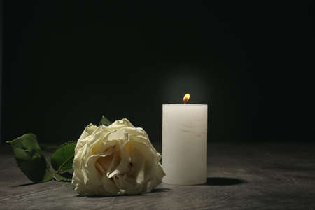 Beautiful white rose and candle on table against black background. Funeral symbol