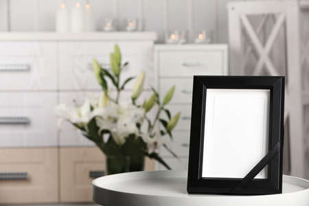 Funeral photo frame with black ribbon on table, indoors Stock Photo