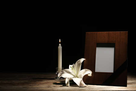 Funeral photo frame, burning candle and white lily on dark background