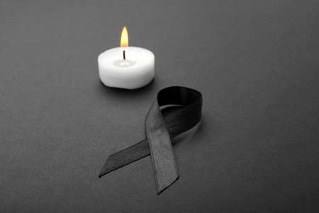 Ribbon and candle on black background. Funeral symbols