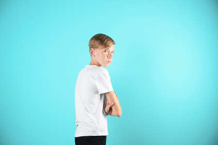 Portrait of young boy standing against color background