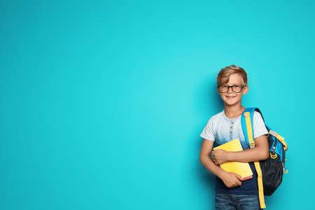 Kleines Schulkind mit Rucksack und Heften auf farbigem Hintergrund