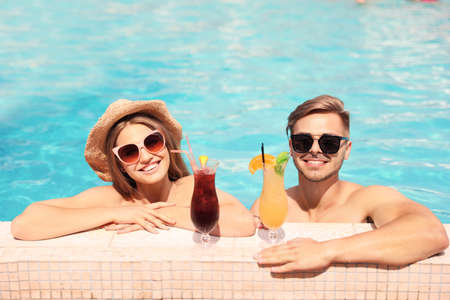 Young couple with cocktails in pool on sunny day Stok Fotoğraf