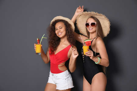 Beautiful young women in beachwear with cocktails on dark background