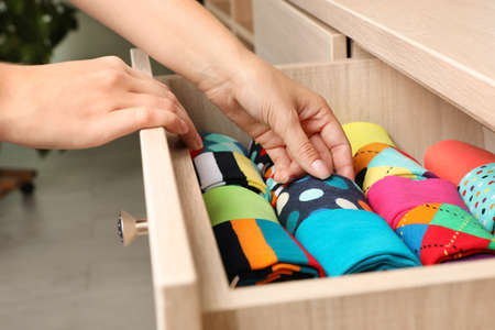 Kobieta otwiera szufladę z różnymi kolorowymi skarpetkami w pomieszczeniu, zbliżenie