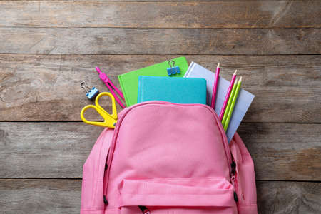 Flat lay composition with backpack and school stationery on wooden background
